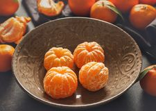 Peeled tangerine in plate. On gray table Stock Photography