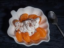 Peeled tangerine with whipped cream, sprinkled with chocolate chips in a decorative plate. Black background stock image