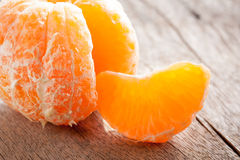 Peeled tangerine on wooden table Stock Photography
