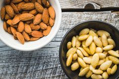 Peeled and unpeeled almonds royalty free stock images