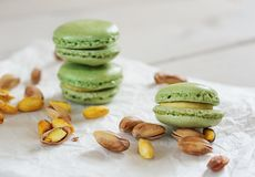 Peeled and unpeeled pistachio nuts  and pistachio flavored macar. Ons presented on a white napkin presented Stock Image