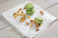 Peeled and unpeeled pistachio nuts  and pistachio flavored macar. Ons presented on a white napkin presented Stock Photos
