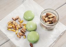 Peeled and unpeeled pistachio nuts  and pistachio flavored macar. Ons presented on a white napkin presented Stock Photography