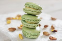 Peeled and unpeeled pistachio nuts  and pistachio flavored macar. Ons presented on a white napkin presented Stock Photo