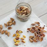 Peeled and unpeeled pistachio nuts presented on a white napkin.  Royalty Free Stock Photography