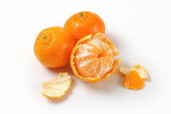 Peeled and unpeeled tangerines Stock Photography