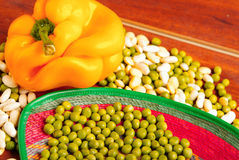 Peeled and unpelaed green lima beans mixed with orange capsicum on wooden surface Royalty Free Stock Image