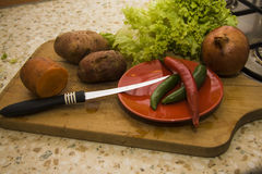 Peeled vegetables with knife and desk Stock Image
