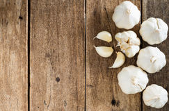 Peeled white garlic on brown wood table Royalty Free Stock Photos