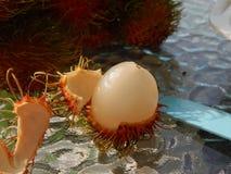 Peelen och frukten av rambutanen Thailand Samui December 13, 2013 Arkivfoto