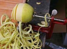 Peeler της Apple με την μισό-ξεφλουδισμένη Apple Στοκ εικόνες με δικαίωμα ελεύθερης χρήσης