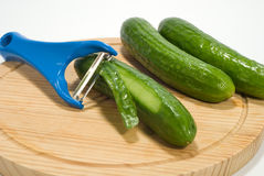 Peeler. And cucumber on a wooden plate stock images