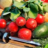 Peeler and fresh organic radish Stock Photo