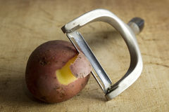 Peeler and potatoes Royalty Free Stock Images