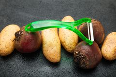 Peeler and root vegetables on a black table stock photos