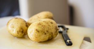 Peeler y patatas fotos de archivo