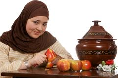 Peeling an apple. Young islamic woman preparing food and peeling an apple Stock Photos