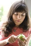 Peeling an apple. A young woman peels a green apple with a small knife Stock Photos