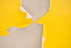 Peeling Away. Yellow paint peeling off of cement Stock Image