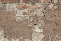 Peeling beige paint on a brick wall in vintage style. Vintage house facade. Empty space. Grunge background. old wall cement backgr stock images