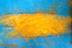 Peeling blue orange paint on a metal surface Stock Images