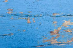 Peeling blue paint on wooden board with cracks. Vintage background stock photography
