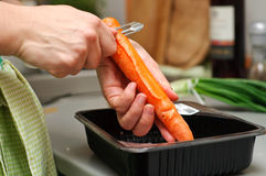 Peeling carrot. A chef peeling a carrot for cooking royalty free stock photo