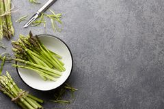 Peeling and cooking fresh raw asparagus. On stone kitchen countertop, top view Royalty Free Stock Image