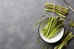 Peeling and cooking fresh raw asparagus. On stone kitchen countertop, top view Royalty Free Stock Photography