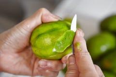 Peeling and cutting ambarella Stock Images