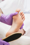 Peeling feet pedicure procedure in SPA salon. royalty free stock photo