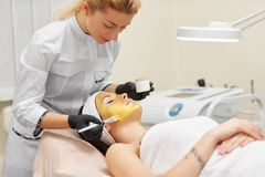 Cosmetologist doing beauty procedure for patient. Royalty Free Stock Photo