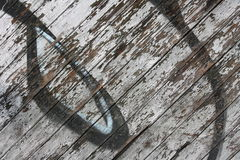 Peeling graffiti on wooden wall. Close-up view of an old wooden wall with peeling paint and graffiti royalty free stock photo