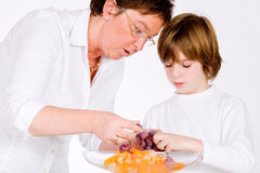 Peeling the grapes. Mother and son making a healthy fruit salad Royalty Free Stock Image