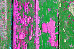 Peeling green and pink paint on old weathered wood - textured background Stock Image
