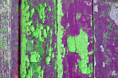 Peeling green and purple paint on old weathered wood - textured background Stock Photos