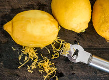 Peeling lemon rind to add zest. To cook stock photography
