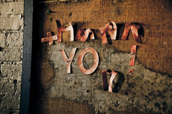Peeling letters spelling Thank You. Decrepit letters hung on a bulletin board long ago Royalty Free Stock Photos