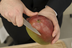 Peeling a mango Royalty Free Stock Photography