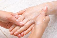 Peeling or moisturizing procedure. Applying peeling scrub or moisturizing cream onto the hands Stock Photography