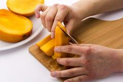 Peeling Off The Fruit Flesh From The Mango Skin Stock Photo