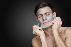 Peeling off. Portrait of a beautiful young man peeling off a facial mask, face and body skin care retreat royalty free stock photography