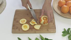 Peeling Oranges Fruits on a Wooden Copping Board. Fruit Ice Cubes Preparation Process stock footage