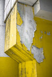 Peeling paint. Close up of an old pillar with yellow peeling paint stock photo