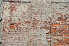 Peeling paint creates pattern on brick wall. In the sun stock photos