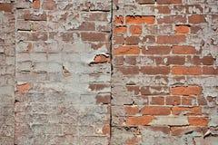 Peeling paint creates pattern on brick wall. In the sun stock images