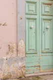 Peeling paint door. Old Maltese townhouse door with peeling paint falling into disrepair. Pastel colours pink and mint green. Ghaxaq, Malta Stock Image