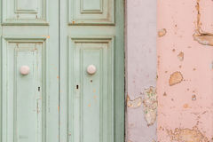 Peeling paint door. Old Maltese townhouse door with peeling paint falling into disrepair. Pastel colours pink and mint green. Ghaxaq, Malta Royalty Free Stock Image