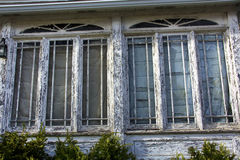 Peeling paint on a house that needs repair, Massachusetts. Windows on a house that badly needs painting. White paint is chipping and peeling off the wood around Royalty Free Stock Photography