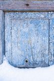 Peeling paint on the old door in the snow. A pattern of rustic blue grunge material. Abstract background. Stock Photo